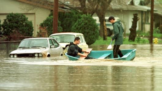 Residents paddle through their neighborhood street in Petaluma, California, on Feb. 19, 1998.