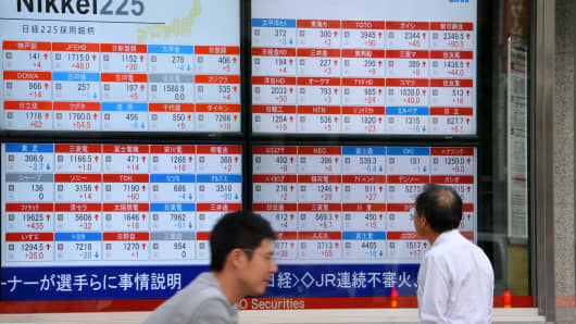 A man looks at an electronic board showing movement of the Nikkei 225 at the Tokyo Stock Exchange in Tokyo, Japan.