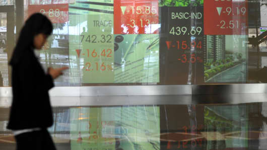 An Indonesian worker walking next to a screen featuring market trading information at the Indonesia Stock Exchange (IDX) in Jakarta.
