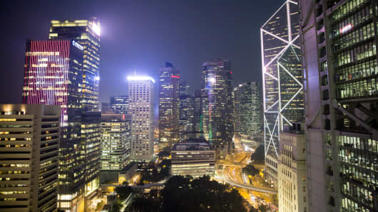 Commercial buildings stand illuminated in the Central business district of Hong Kong, China.