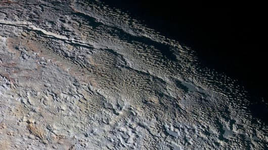 The Tartarus Dorsa mountains rise up along Pluto's day-night terminator and show intricate but puzzling patterns of blue-gray ridges and reddish material in between.