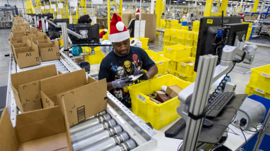 Amazon.com employees load boxes with orders at the company's fulfillment center ahead of Cyber Monday in Tracy, California.