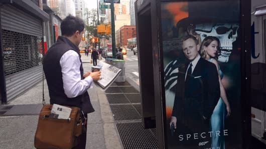 A pedestrian reads a paper near a James Bond Spectre 007 movie poster in New York.