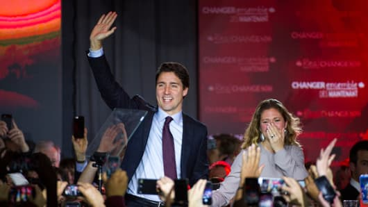 Justin Trudeau, Canada's prime minister-elect and leader of the Liberal Party of Canada, and his wife Sophie Gregoire-Trudeau wave to supporters on election night.