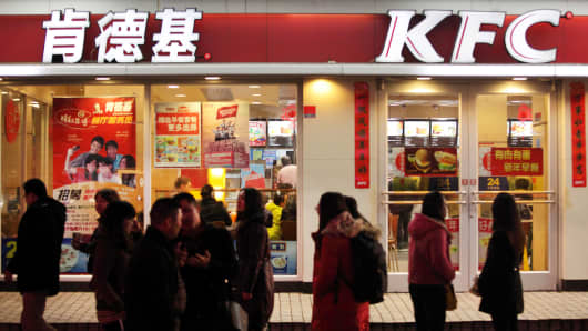 Pedestrians walk past a Yum! Brands' KFC restaurant in Shanghai.