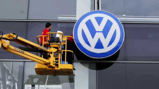 Workers clean the facade of a Volkswagen dealership.