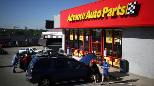 Customer vehicles sit parked outside an Advance Auto Parts automotive supply store in La Grange, Kentucky.