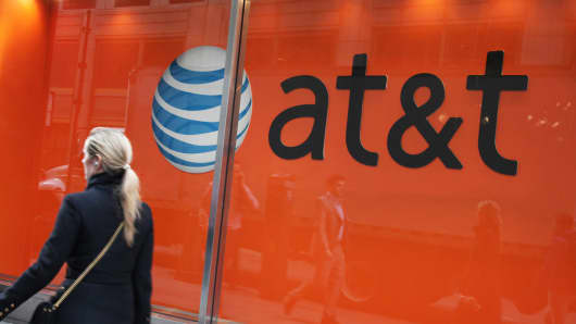 A pedestrian walks past an AT&T sign in New York.