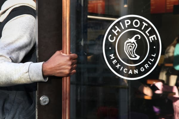 A man opens the door to a Chipotle restaurant in New York.