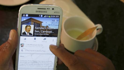 A person uses a smartphone to look at the Facebook page of Cambodia's Prime Minister Hun Sen.