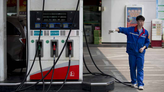 An employee directs a vehicle toward gas pumps at a China Petroleum & Chemical Corp. (Sinopec) gas station in the Zhujiang New Town district of Guangzhou, Guangdong Province, China.