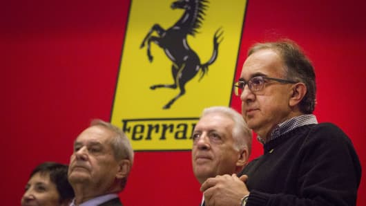 Sergio Marchionne, chief executive officer of Fiat Chrysler Automobiles NV (FCA), right, and Piero Ferrari, vice chairman of Ferrari SpA, second right, look on after ringing the opening bell of the New York Stock Exchange (NYSE) in New York, U.S., on Wednesday, Oct. 21, 2015