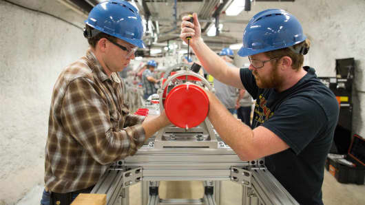 Graduate students Thomas Kadlecek, left, and PHD student Tyler Borgwardt, both from the South Dakota School of Mines and Technology, assemble the Compact Accelerator System for Performing Astrophysical Research, otherwise known as CASPAR, at the Sanford Underground Laboratory in Lead, South Dakota.