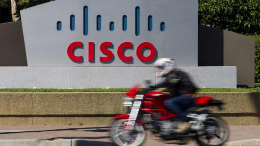 A motorcyclist rides past Cisco Systems Inc. signage at the company's headquarters in San Jose, California.