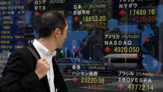 A pedestrian walks in front of a share prices board showing the numbers on the Nikkei 225 at the Tokyo Stock Exchange in Tokyo, Japan.