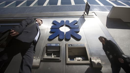A logo sits above an automated teller machine (ATM) outside a Royal Bank of Scotland Group (RBS) bank branch in London, U.K.