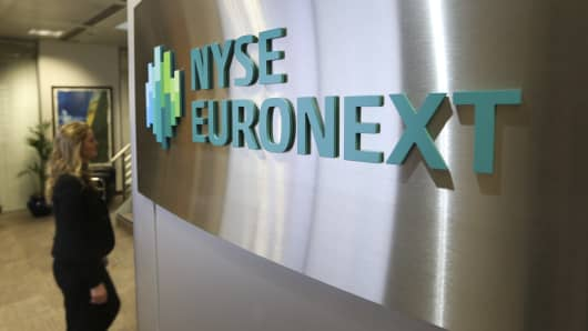 A visitor passes a sign on the wall inside the offices of the NYSE Euronext exchange in London.