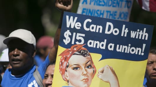 A protester holds a sign in Upper Senate Park during a rally on Capitol Hill in Washington, D.C., on Wednesday, July 22, 2015, to push for a raise to $15 an hour for the minimum wage.