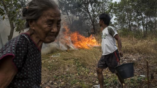 A man carries a bucket of water to try to extinguish the fire on burned peatland and fields near his house at Ogan Ilir district on October 3, 2015 in Palembang, South Sumatra, Indonesia.