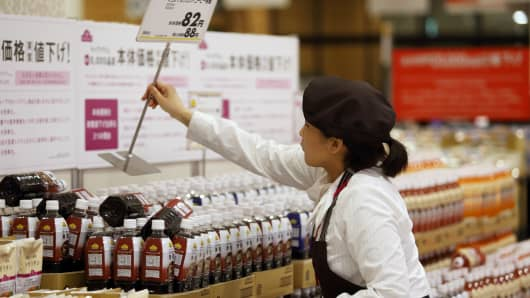 An employee places a new price sign on bottles of coffee at an Aeon Co. supermarket in Chiba, Japan.