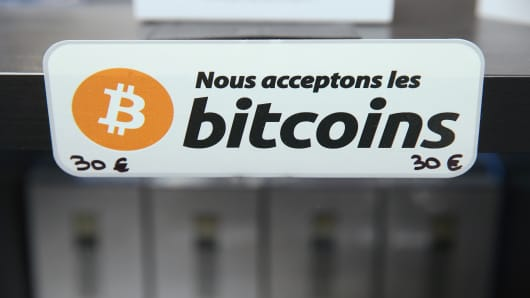 A sign in French that reads: 'We accept bitcoins' hangs at a display of the LedgerWallet Nano USB stick that enables security-protected transactions with bitcoins at the 2015 CeBIT technology trade fair on March 16, 2015 in Hanover, Germany