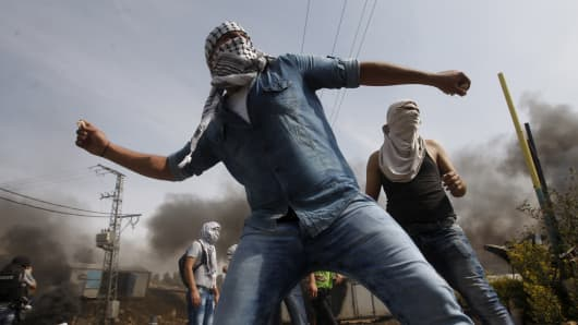 A Palestinian protester hurls stones toward Israeli troops during clashes in the West Bank city of Hebron, October 18, 2015.