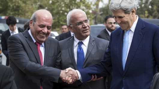 U.S. Secretary of State John Kerry shakes hands with an official as he arrives for a meeting with Palestinian President Mahmoud Abbas at Abbas' residence in Amman, October 24, 2015. In the middle is Saeb Erekat, the secretary-general of the Palestine Liberation Organization.