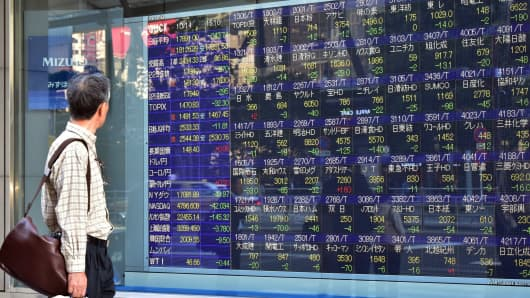 A man looks at a share prices board in Tokyo, Japan.