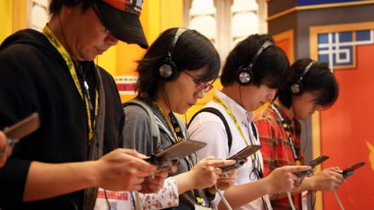 Attendees play video games on a Nintendo device in Chiba, Japan.
