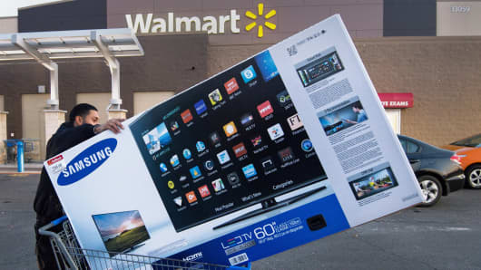 A Black Friday shopper pushes his TV after purchasing it at a Walmart in Fairfax, Virginia.
