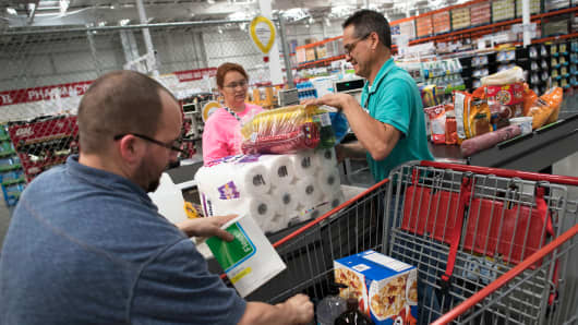 Employees load a customers purchases into a shopping cart at a Costco store in East Peoria, Illinois.