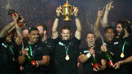 Richie McCaw of New Zealand lifts the Webb Ellis Cup as his team-mates spray champagne after victory in the 2015 Rugby World Cup Final match between New Zealand and Australia on October 31, 2015 in London, United Kingdom.