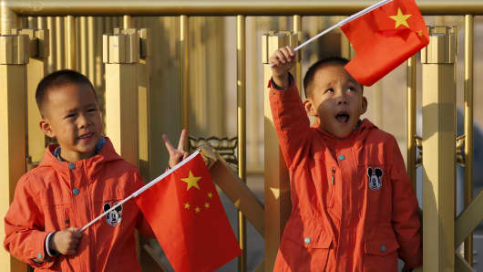 Twin boys Sun Qiyu and Sun Qichun hold China's national flags on the Tiananmen Gate in Beijing November 2, 2015.