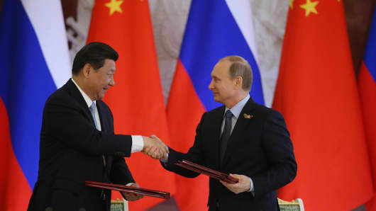 Russian President Vladimir Putin (R) shakes hands with Chinese President Xi Jinping.