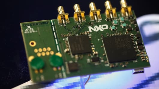 Microprocessors sit on a circuit board displayed on the NXP Semiconductors NV pavilion at the Mobile World Congress in Barcelona, Spain, on Monday, March 2, 2015.