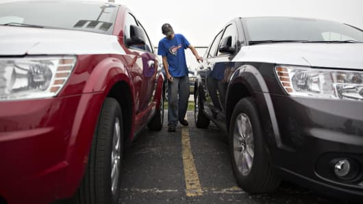 A detail manager looks over a 2016 FCA US LLC Dodge Journey during a new vehicle delivery inspection at the Key Auto Mall car dealership in Moline, Illinois.