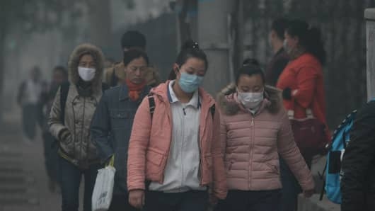 Citizens wearing face masks walk in heavy smog on November 3, 2015 in Harbin, Heilongjiang Province of China. Heavy smog stroke northeast China with the visibility in parts of cities reaching less than 50 meters.