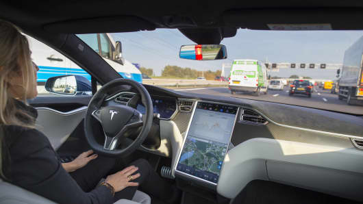 An employee operates a Tesla Motors Model S electric automobile, equipped with Autopilot hardware and software, hands-free on a highway in Amsterdam, Netherlands.