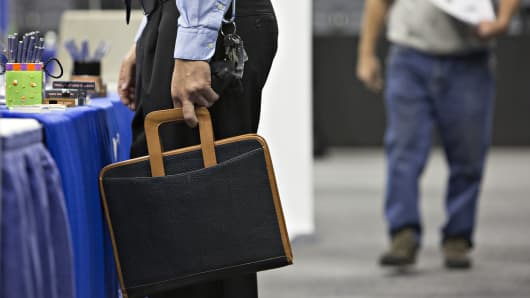 A job seeker holds a briefcase while speaking with recruiters during the Quad Cities career fair in Moline, Illinois.
