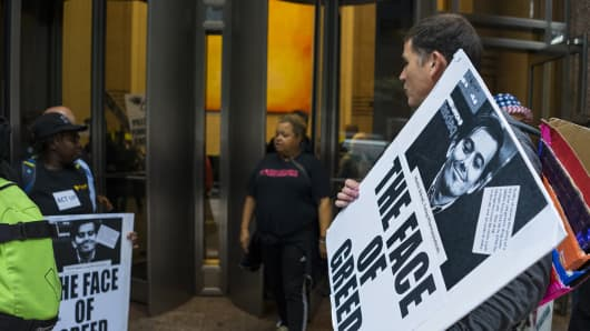 Activists hold signs containing the image of Turing Pharmaceuticals CEO Martin Shkreli in front the building that houses Turing's offices, in New York, Thursday, Oct. 1, 2015, during a protest highlighting pharmaceutical drug pricing.