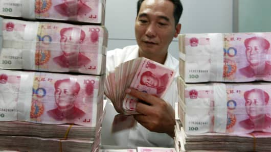 Chinese bank staff member counting stacks of 100-yuan notes at a bank in Huaibei, China.