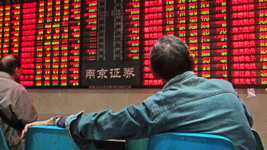 An investor observes stock market at a stock exchange hall in Nanjing, Jiangsu Province of China.