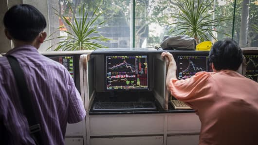 Investors stand at trading terminals at a securities exchange house in Shanghai, China.