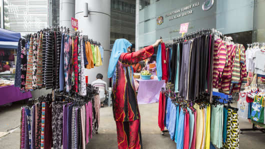 A woman looks at clothing at a market stall in Putrajaya, Malaysia.