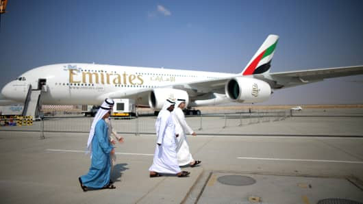Businessman walk past an Emirates Airbus A380 during the Dubai Airshow on November 18, 2013 in Dubai, United Arab Emirates.