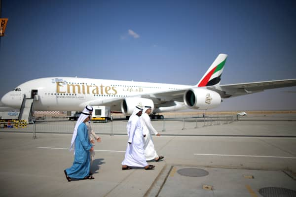 Businessman walk past an Emirates Airbus A380 during the Dubai Airshow on November 18, 2013 in Dubai, United Arab Emirates.