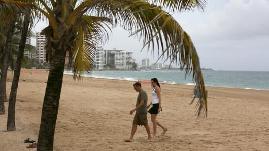A couple walks on the beach in San Juan, Puerto Rico.