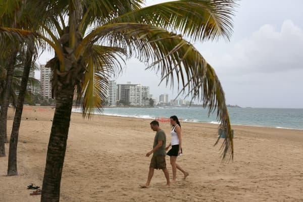 A couple walks on the beach in San Juan, Puerto Rico.