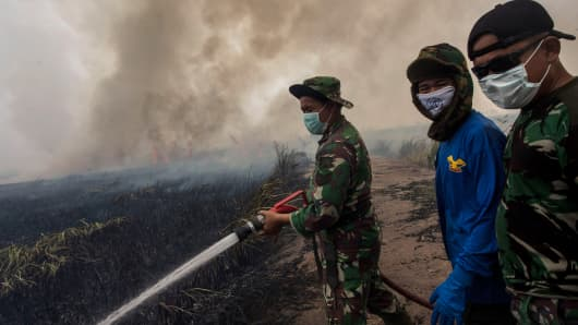 Indonesian soldiers extinguish the fire on burned peatland and fields on October 2, 2015 in Palembang, South Sumatra, Indonesia.
