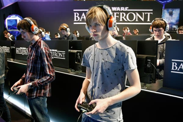 Visitors play a video game 'Star Wars Battlefront' at the Paris Game Week, a trade fair for video games on October 28, 2015 in Paris.